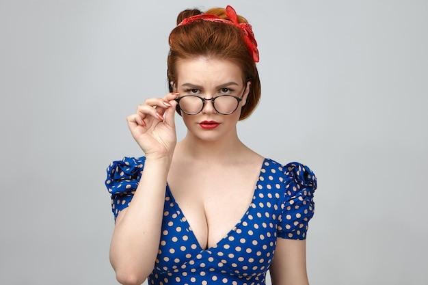 Studio shot of attractive young serious caucasian woman teacher in vintage outfit having strict look, lowering stylish eyeglasses and staring at camera, posing isolated against blank wall background