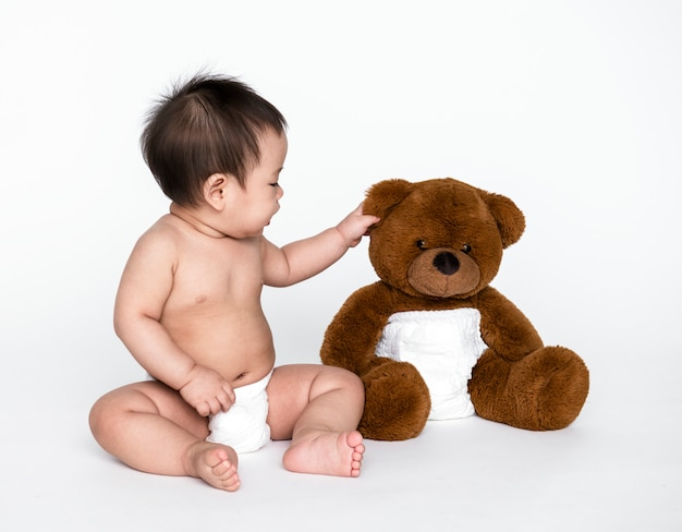 Studio shot of a baby with a teddy bear