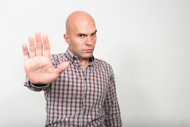 Studio shot of bald businessman against white background