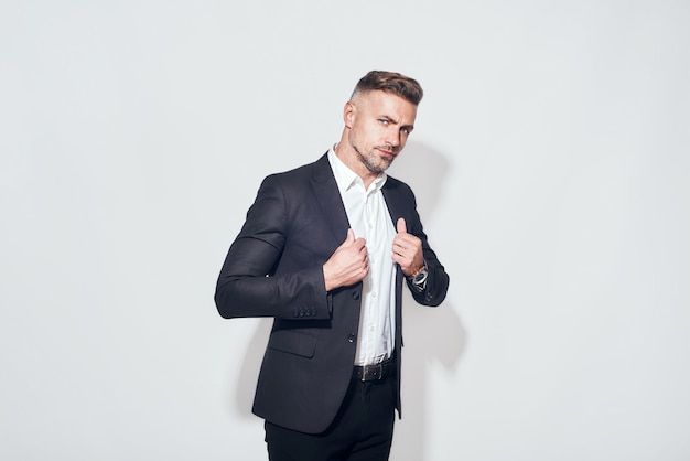Studio shot of bearded businessman in classic suit adjusting jacket and looking at camera while standing against grey background. business look. studio shot