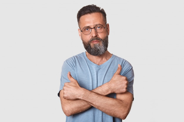Studio shot of bearded serious guy dresses gray t shirt and sunglasses