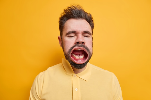 Studio shot of bearded tired caucasian man closes eyes keeps mouth widely opened while yawning has sleepy expression dressed in shirt