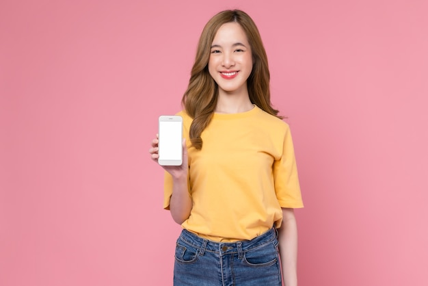 Studio shot of beautiful asian woman holding smartphone and smiling on light pink background
