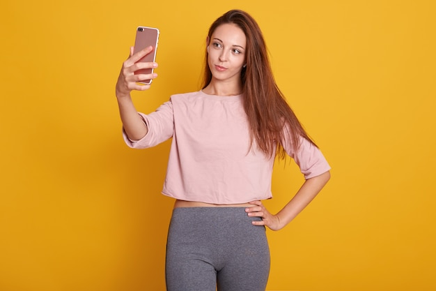 Studio shot of beautiful brown haired woman with straight hair in gray trousers and rose shirt taking selfie