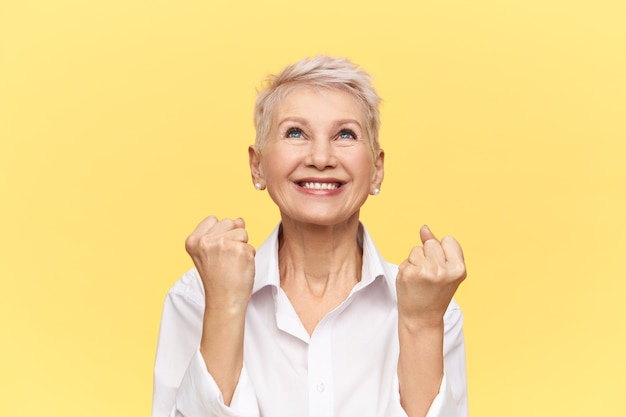 Studio shot of beautiful energetic mature businesswoman with pixie hairstyle exclaiming yes, looking up with happy smile, clenching fists, celebrating good deal.
