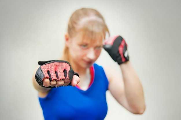 A studio shot of beautiful fitness woman training boxing or functional exercise. the girl shows the fist. training melee. women's fight without rules. body, healthy, lifestyle,