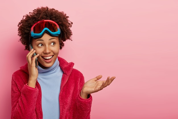Studio shot of beautiful happy curly woman gestures and smiles, wears ski goggles.