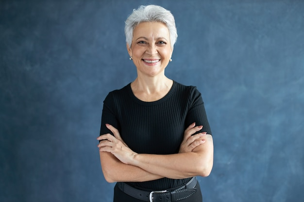 Studio shot of beautiful happy retired caucasian female with pixie hairdo crossing arms on her chest, having confident look, smiling broadly