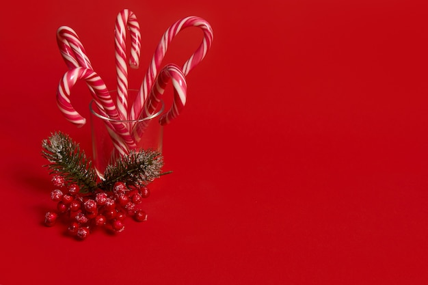 Studio shot of beautiful minimalistic simple composition with christmas lollipops in transparent glass and snowy branch of pine with red berries, holly, on red background with copy space for ad