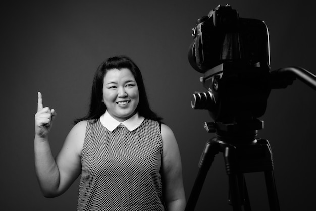 Studio shot of beautiful overweight asian woman wearing dress against gray background in black and white