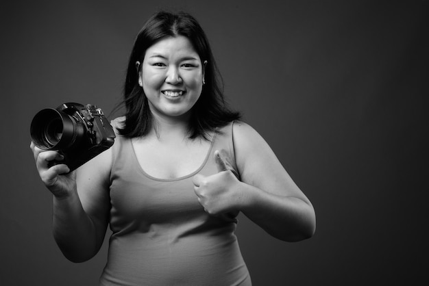 Studio shot of beautiful overweight asian woman wearing sleeveless dress against gray background in black and white