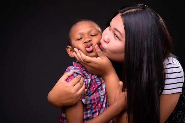 Studio shot of beautiful overweight asian woman and young multi-ethnic asian boy together against black background