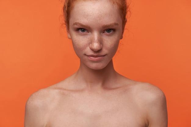 Studio shot di bella giovane donna con i capelli rossi nel nodo in piedi su sfondo arancione con le mani verso il basso, sorridendo dolcemente alla telecamera con il sopracciglio alzato. linguaggio del corpo di espressione facciale di emozioni umane