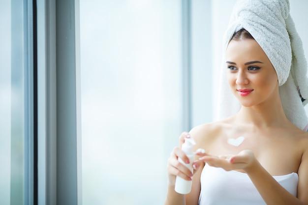 Studio shot of beautiful young woman applying moisturizer cream onto her face in modern bathroom