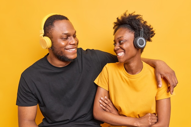 Studio shot of best friends with dark skin have pleasant talk smile happily show white teeth listen music via wireless headphones
