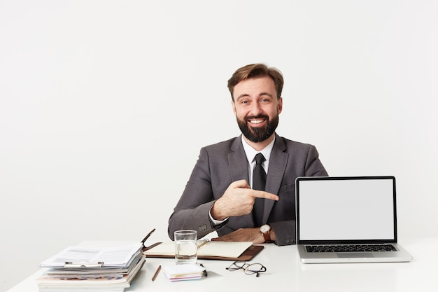 Studio shot of brunette bearded guy with short haircut posing over white wall in formal clothes, showing on his laptop with raised hand and looking cheerfully at front
