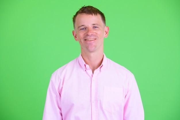 Studio shot of businessman wearing pink shirt against green background