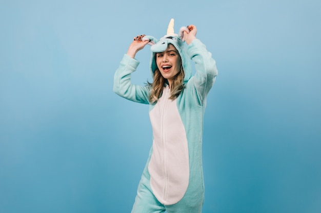 Studio shot of carefree woman in unicorn suit