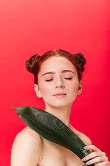 Studio shot della ragazza caucasica che tiene foglia verde con gli occhi chiusi. ginger donna nuda con pianta isolata su sfondo rosso.