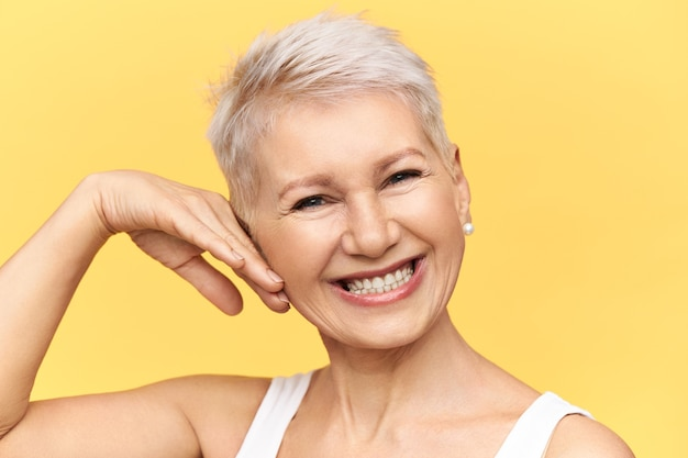 Studio shot of charismatic positive middle aged female posing against yellow background touching cheek, looking at camera with broad cheerful smile, taking care of her wrinkled skin, applying cream
