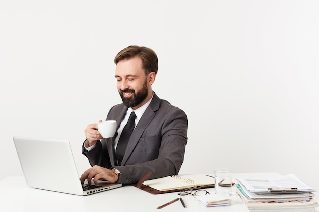 Studio shot of cheerful bearded brunette guy in formal clothes working in office with laptop and his notes, keeping hand and keyboard while having cup of coffee