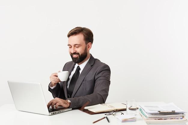 Studio shot di allegro barbuto brunette guy in abiti formali che lavorano in ufficio con il computer portatile e le sue note, mantenendo la mano e la tastiera mentre si sorseggia una tazza di caffè