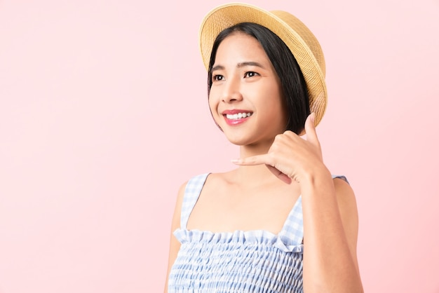 Studio shot of cheerful beautiful asian woman in blue color dress and wearing a hat with calling hand show and stand on pink background.