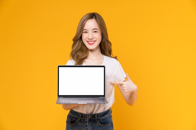 Studio shot of cheerful beautiful asian woman in white t-shirt and holding laptop mockup of blank screen on yellow background.