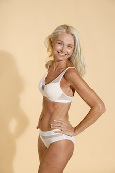 Studio shot of cheerful caucasian mature woman in lingerie smiling away while standing isolated