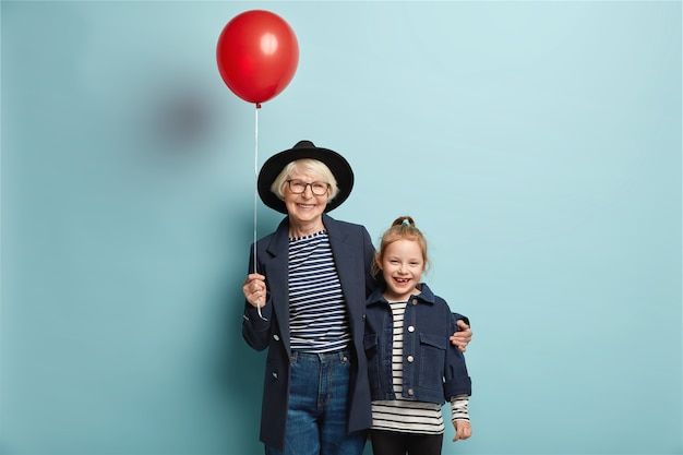 Studio shot of cheerful granddaughter and grandmother embrace together, come on party