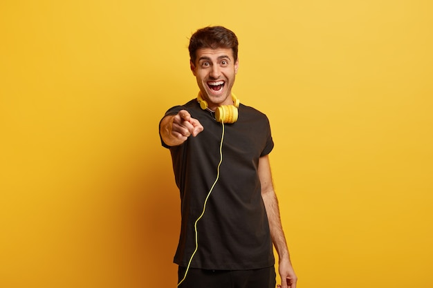 Studio shot of cheerful hipster guy makes choice stretches fore finger at camera
