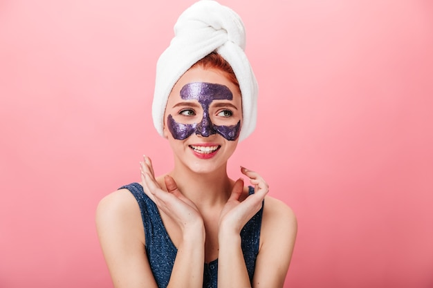 Studio shot of cheerful lady with face mask. excited girl in towel on head posing on pink background.