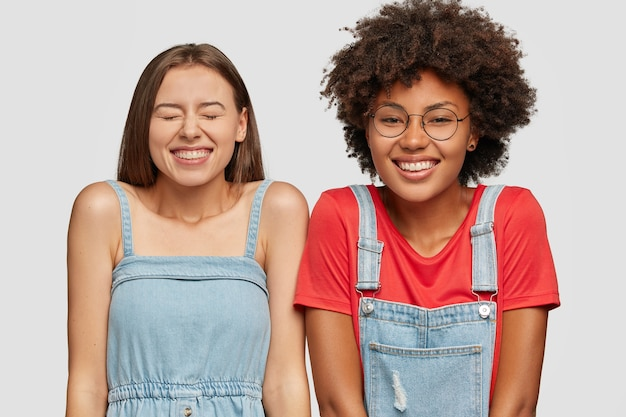 Studio shot di allegre donne di razza mista ridono felicemente al buon scherzo