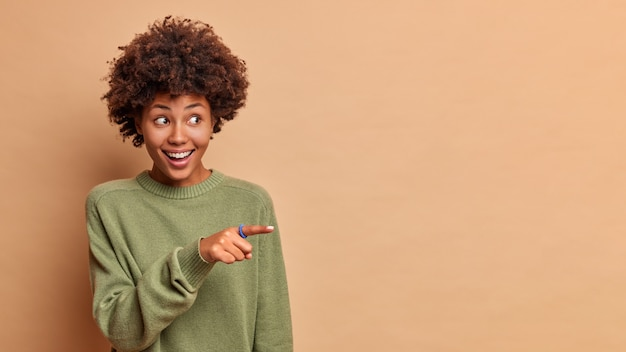 Studio shot of cheerful pleased woman with curly hair points away on copy space laughs happily advertises promo dressed casually isolated over beige wall