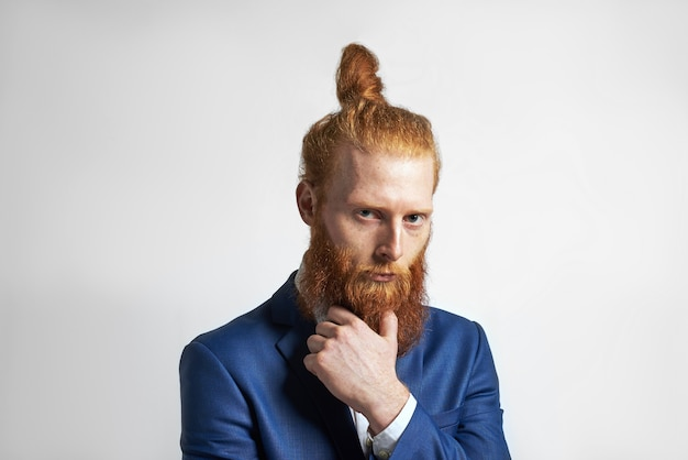 Studio shot of confident stylish young redhaired businessman with hair bun and fuzzy beard, holding hand on chin and looking at camera with pensive expression, thinking about business ideas and plans