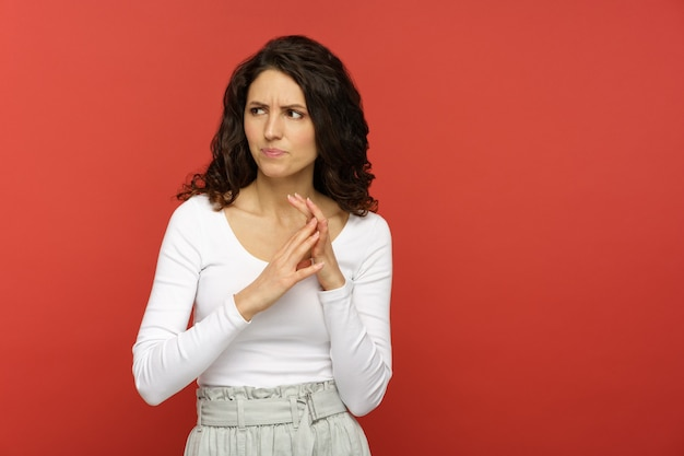 Studio shot of confused pensive girl with hands in front of body think of problem solution look side