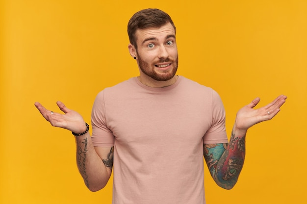 Studio shot of confused tattooed young man in pink tshirt with beard holding copyspace at both palms over yellow wall looking at front