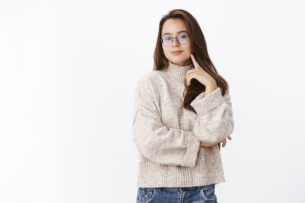Studio shot of creative and happy stylish caucasian girl in glasses and sweater holding hand crossed over chest and touching chick looking curiously at front as having interesting idea. body language