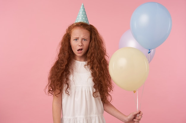 Studio shot of curly redhead female kid holding air balloons in hand while standing over pink background, wearing white dress and birthday cap, frowning and looking at camera with confused face
