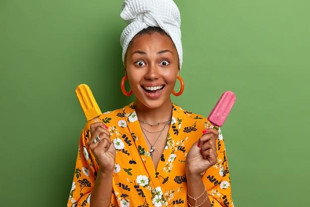 Studio shot of dark skinned afro american woman smiles positively