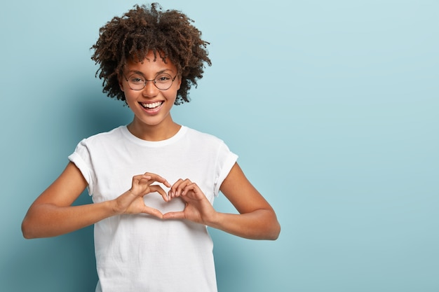 Studio shot of delighted female model sends heart gesture, confesses in love, looks at camera happily