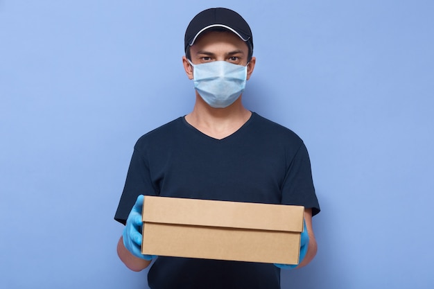 Studio shot of delivery man dresses cap, t shirt, medical mask and latex gloves, wears protective closing while working to protect himself from dangerous corona virus