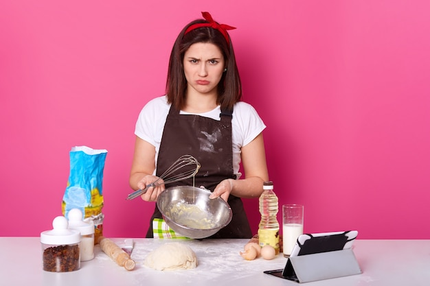 Studio shot of disappointed brunette housewife standing at kitchen with unpleasant facial expression, holding bowl and whisk in both hands, failed to mix all ingredients in proper way, frown face.