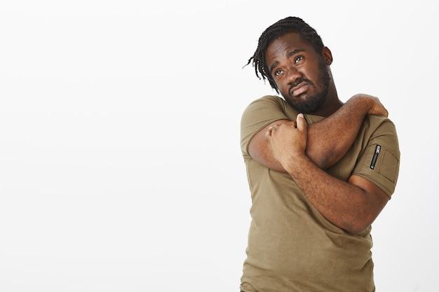 Studio shot del ragazzo deluso in una maglietta marrone in posa contro il muro bianco