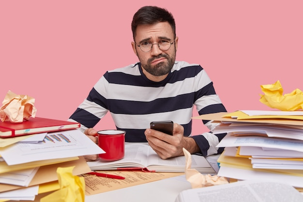 Studio shot of displeased caucasian man frowns face, holds cellular in hand, recieves message with tasks to do, wears striped jumper, drinks hot coffee or tea