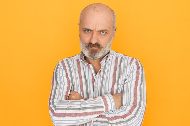 Studio shot of displeased grumpy stubborn male pensioner with thick gray beard crossing arms on his chest and staring at camera from under brows, having angry look.