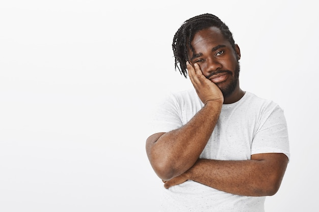 Studio shot of displeased guy with braids posing against the white wall