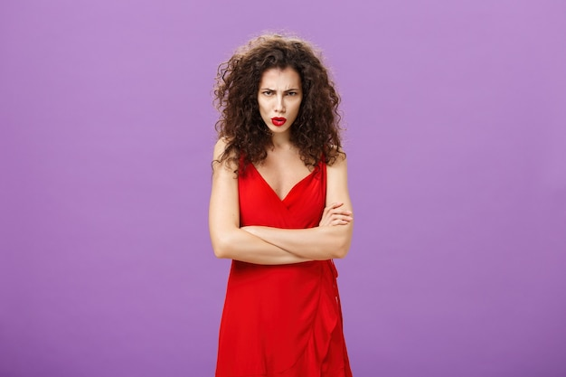 Studio shot of displeased and offended outraged woman in elegant red evening dress crossing arms aga...