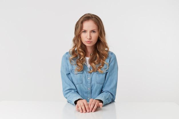 Studio shot di scontento giovane bella donna con lunghi capelli biondi ondulati, indossa una camicia di jeans, ubicazione al tavolo, accigliato e guardando la telecamera isolata su sfondo bianco.