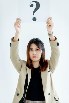 Studio shot of doubtful female officer staff in business suit look at camera holding question mark paper cardboard sign raise overhead showing curiosity thinking for answers on white background.
